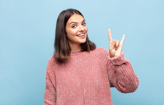 Молодая красивая женщина чувствует себя счастливой, веселой, уверенной, позитивной и мятежной, делая знак рок или хэви-метал рукой