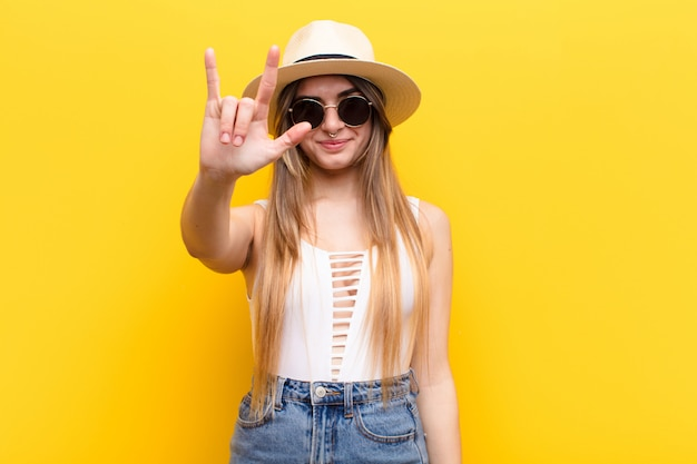 Молодая красивая женщина, чувствуя себя счастливой, веселой, уверенной, позитивной и бунтарской, делая знак рок или хэви-метал рукой