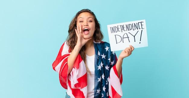 幸せを感じて、口の隣の手で大きな叫びを与える若いきれいな女性独立記念日のコンセプト