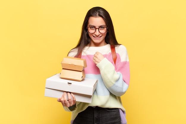 Молодая красивая женщина чувствует себя счастливой, позитивной и успешной, мотивированной, когда сталкивается с проблемой или празднует хорошие результаты. возьмите концепцию быстрого питания aeay
