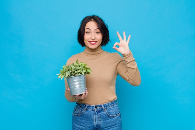 Young pretty woman feeling happy, relaxed and satisfied, showing approval with okay gesture, smiling with a plant
