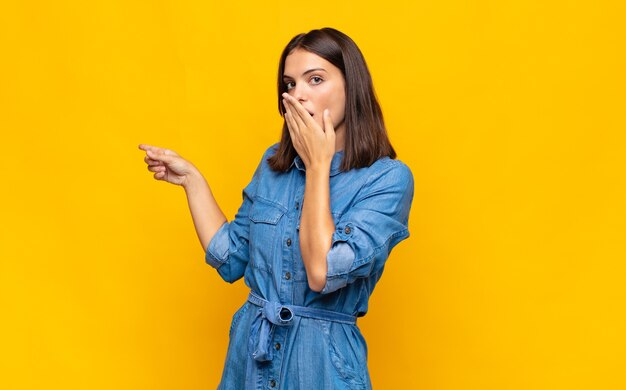 Young pretty woman feeling happy, shocked and surprised, covering mouth with hand and pointing to lateral copy space