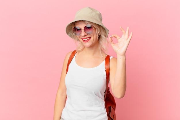 幸せを感じて、大丈夫なジェスチャーで承認を示す若いきれいな女性。夏の観光コンセプト