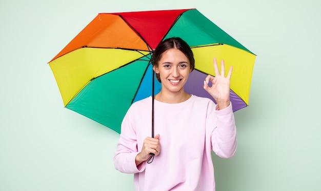 젊고 예쁜 여자가 행복해하며 괜찮은 제스처로 승인을 보여줍니다. 우산 개념