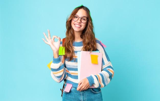 幸せを感じ、バッグを持って大丈夫なジェスチャーで承認を示し、本を持っている若いきれいな女性