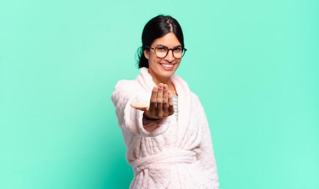 Молодая красивая женщина чувствует себя счастливой, успешной и уверенной в себе, сталкивается с проблемой и говорит: давай, давай! или приветствуя вас. концепция пижамы
