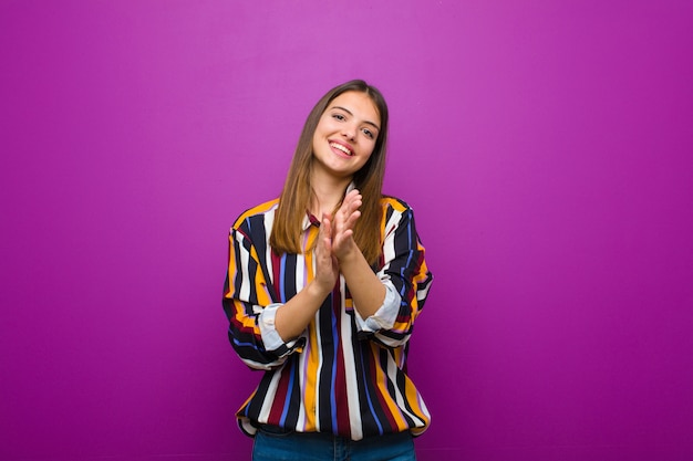 Young pretty woman feeling happy and successful, smiling and clapping hands, saying congratulations with an applause over purple wall
