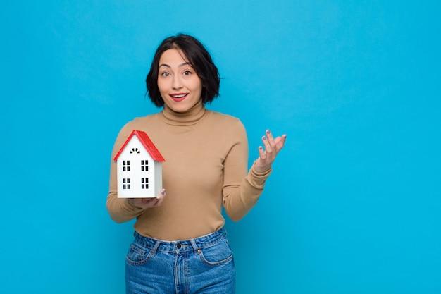 Молодая красивая женщина чувствует себя счастливой, удивленной и веселой, улыбается с позитивным настроем, реализует решение или идею с помощью модели дома