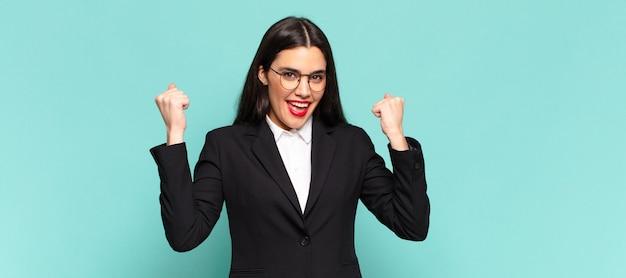 Молодая красивая женщина чувствует себя счастливой, удивленной и гордой, кричит и празднует успех с широкой улыбкой. бизнес-концепция
