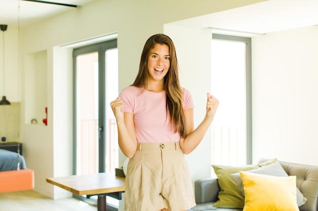 Молодая красивая женщина чувствует себя счастливой, удивленной и гордой, кричит и празднует успех с широкой улыбкой