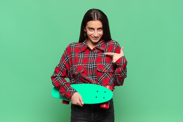 Young pretty woman feeling happy, surprised and proud, pointing to self with an excited, amazed look. skate board concept