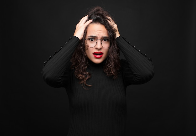 Молодая красивая женщина в ужасе и шоке, поднимает руки к голове и паникует из-за ошибки у черной стены.