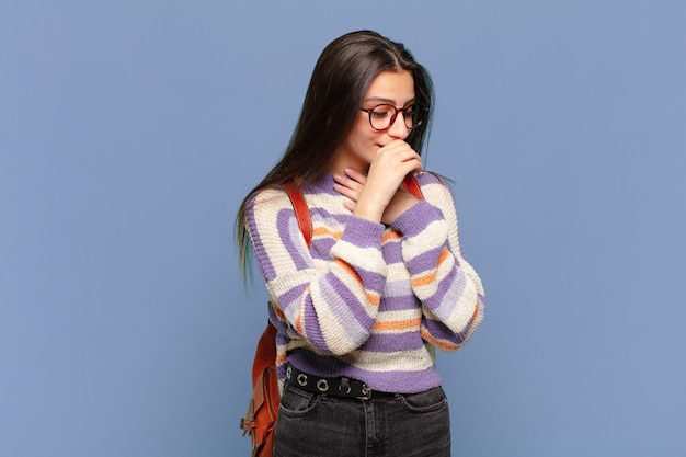 喉の痛みとインフルエンザの症状で気分が悪くなり、口を覆って咳をする若いきれいな女性。学生の概念