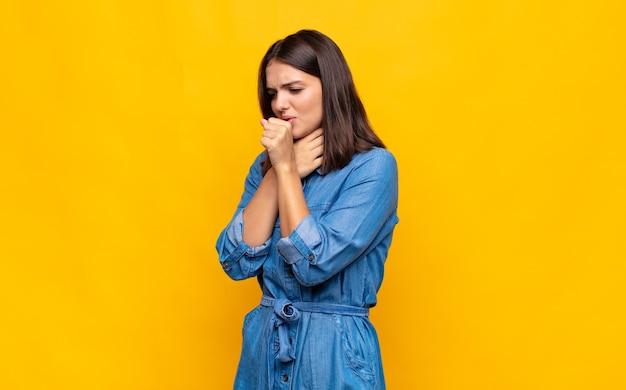 喉の痛みとインフルエンザの症状で気分が悪い若いきれいな女性