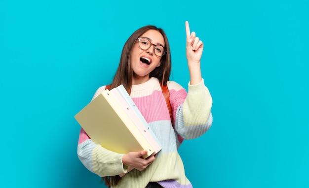 Молодая симпатичная женщина чувствует себя счастливым и взволнованным гением, реализовав идею, весело поднимая палец, эврика!