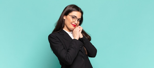 Young pretty woman feeling in love and looking cute, adorable and happy, smiling romantically with hands next to face. business concept