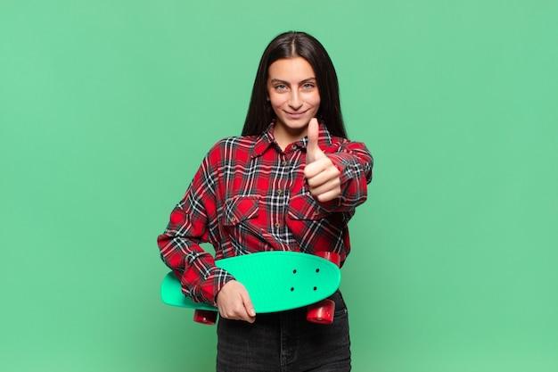 Молодая красивая женщина чувствует себя гордой, беззаботной, уверенной и счастливой, позитивно улыбаясь, подняв палец вверх. скейтборд концепция