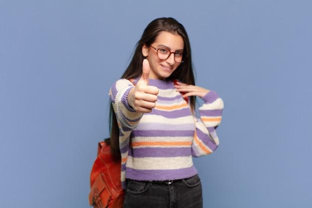 자랑스럽고, 평온하고, 자신감 있고, 행복하고, 엄지 손가락으로 긍정적으로 웃고있는 젊은 예쁜 여자. 학생 개념