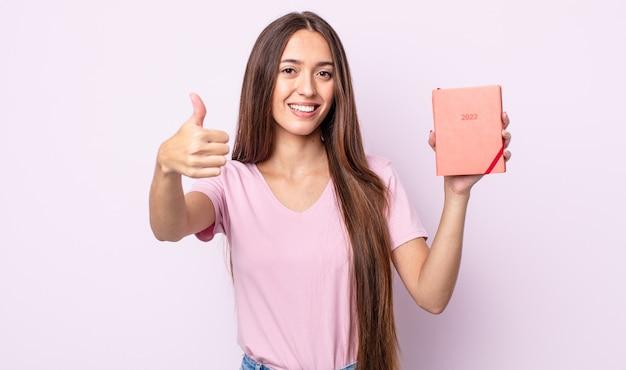親指を立てて前向きに笑って、誇りを感じている若いきれいな女性。 2022プランナーコンセプト