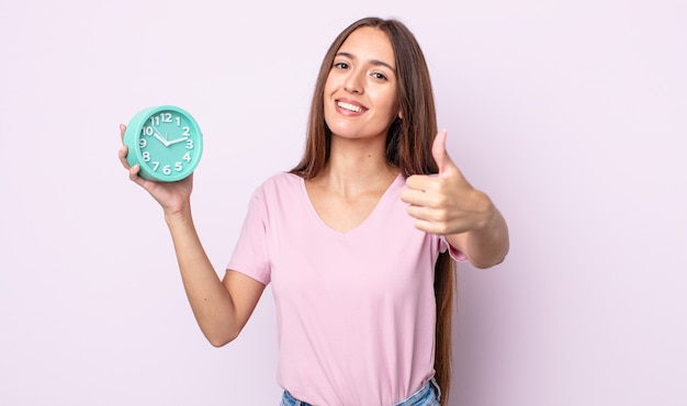 Молодая красивая женщина чувствует себя гордой, позитивно улыбаясь, подняв палец вверх. концепция будильника