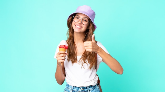 Young pretty woman feeling proud,smiling positively with thumbs up holding an ice cream. summer concept