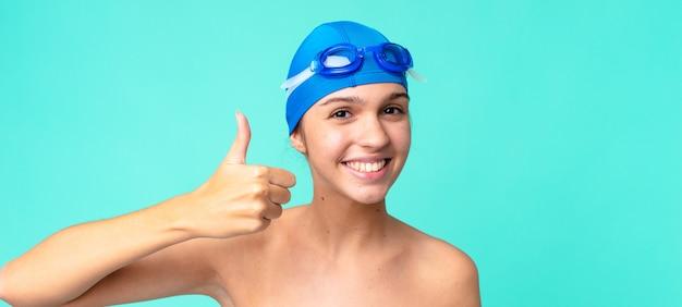 誇りを感じて、水泳用ゴーグルで親指を立てて前向きに笑っている若いきれいな女性