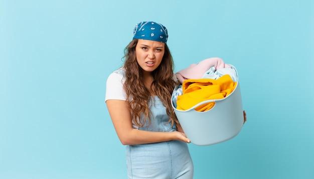 困惑と混乱を感じ、洗濯かごを持っている若いきれいな女性