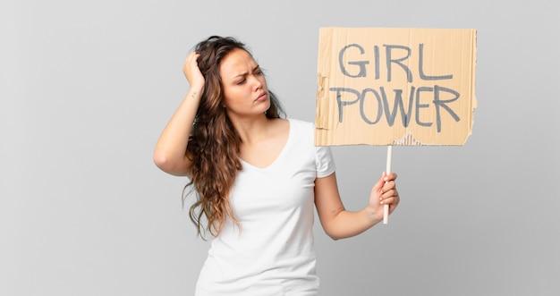 困惑と混乱を感じ、頭を掻き、女の子のパワーバナーを保持している若いきれいな女性