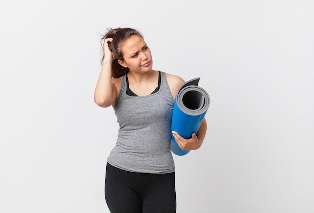 Молодая красивая женщина чувствует себя озадаченной и смущенной, почесывая голову и держа коврик для йоги