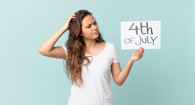 困惑と混乱を感じて、頭の独立記念日の概念を引っ掻く若いきれいな女性