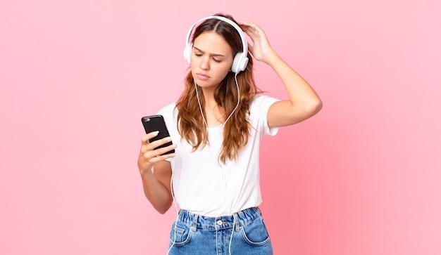 Молодая красивая женщина чувствует себя озадаченной и сбитой с толку, почесывая голову в наушниках и смартфоне