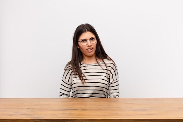 テーブルに座っている予期しない何かを見て、愚かで驚いた表情で困惑し混乱している若いきれいな女性