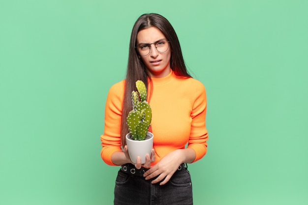 Young pretty woman feeling puzzled and confused, with a dumb, stunned expression looking at something unexpected. cactus concept