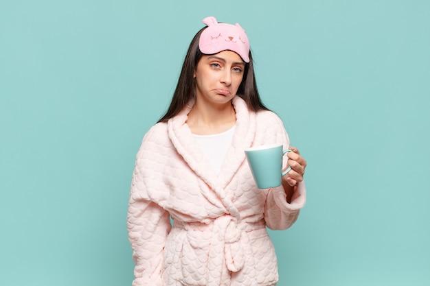 不幸な表情で悲しみと泣き言を感じ、否定的で欲求不満の態度で泣いている若いきれいな女性。パジャマのコンセプトを身に着けて目を覚ます