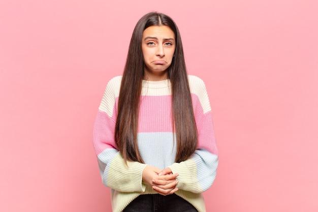 不幸な表情で悲しみと泣き言を感じ、否定的で欲求不満の態度で泣いている若いきれいな女性