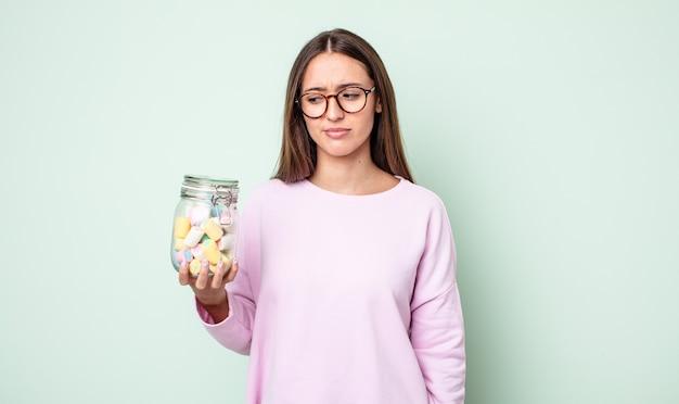 若いきれいな女性は、悲しみ、動揺、または怒りを感じ、横を向いています。ゼリーキャンディーのコンセプト