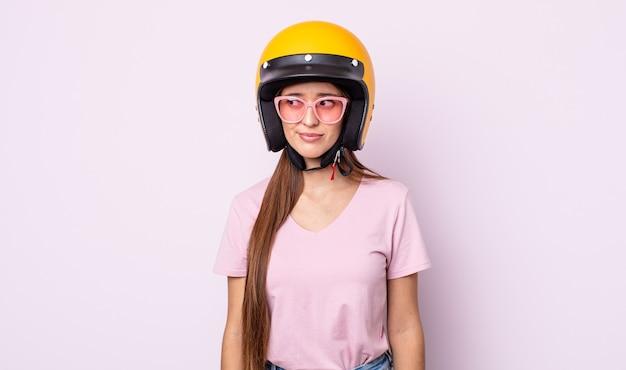 젊은 예쁜 여자는 슬프거나 화가 나거나 화가 나서 옆을 바라보고 있습니다. 오토바이 라이더와 헬멧