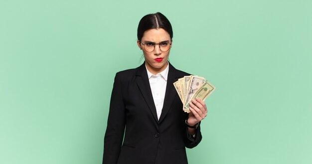 Молодая красивая женщина грустит, расстроена или злится, смотрит в сторону с отрицательным отношением и хмурится в знак несогласия. концепция бизнеса и банкнот
