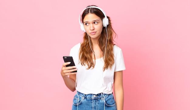 悲しい、動揺または怒りを感じ、ヘッドフォンとスマートフォンで横を向いている若いきれいな女性