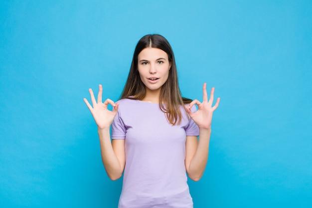 若いきれいな女性がショックを受け、驚いて、驚いて、青い壁に両手で大丈夫のサインを作る承認を示す