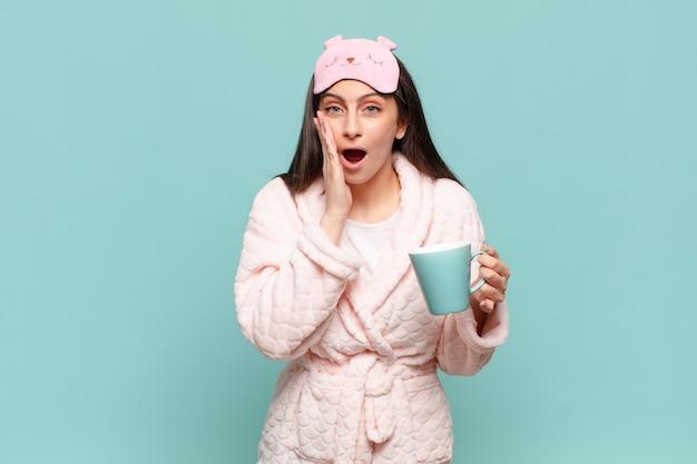 ショックを受けて怖がっている若いきれいな女性は、口を開けて頬に手を当てて恐怖を感じています。パジャマのコンセプトを身に着けて目を覚ます