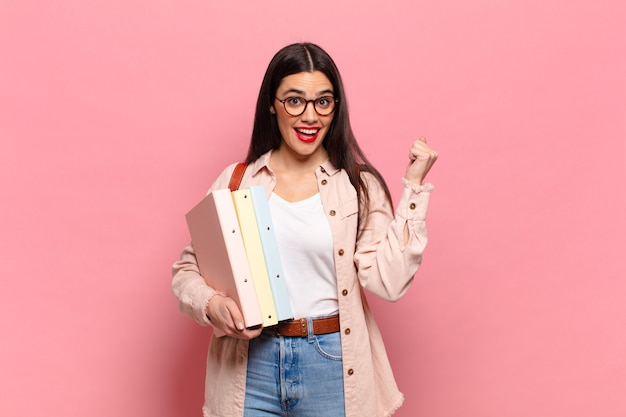 Молодая симпатичная женщина чувствует себя потрясенной, взволнованной и счастливой, смеется и празднует успех, говоря: «вау!». студенческая концепция