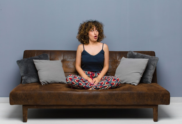 Молодая красивая женщина, чувство шокирован, счастлив, поражен и удивлен, глядя в сторону с открытым ртом, сидя на диване.