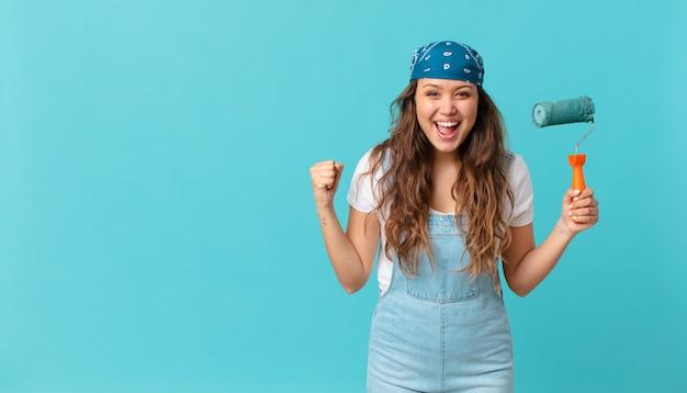Молодая красивая женщина в шоке, смеется, празднует успех и красит стену