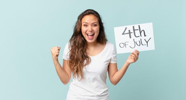 ショックを受け、笑い、成功を祝う独立記念日のコンセプトを感じている若いきれいな女性 Premium写真