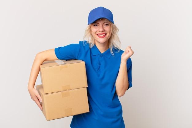 Молодая красивая женщина, чувствуя себя потрясенной, смеясь и празднуя успех. концепция доставки пакетов