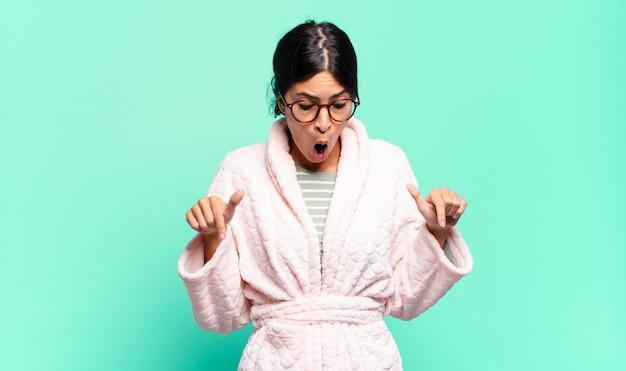若いきれいな女性は、ショックを受け、口を開けて驚いて、不信と驚きで下を向いて見ています。パジャマのコンセプト