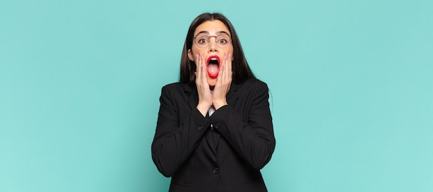 Young pretty woman feeling shocked and scared, looking terrified with open mouth and hands on cheeks. business concept