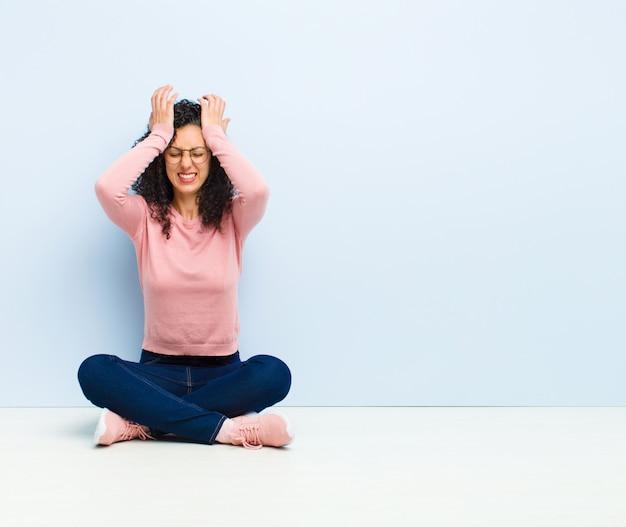 ストレスと不安、落ち込んで頭痛で欲求不満を感じて、床に座って頭に両手を上げる若いきれいな女性