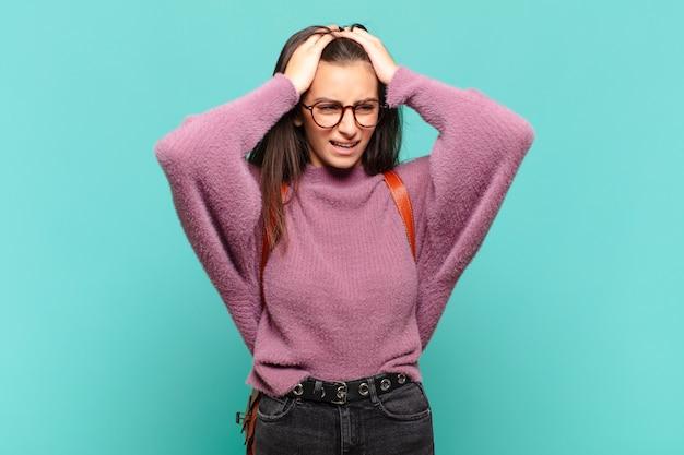 젊고 예쁜 여성은 스트레스와 불안, 우울과 두통으로 좌절감을 느끼며 두 손을 머리 위로 들어 올립니다. 학생 개념